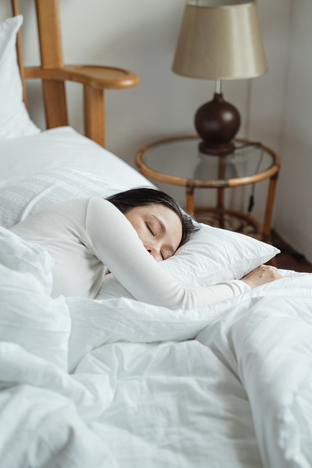 woman sleeping on bed of white blankets to recover from workout