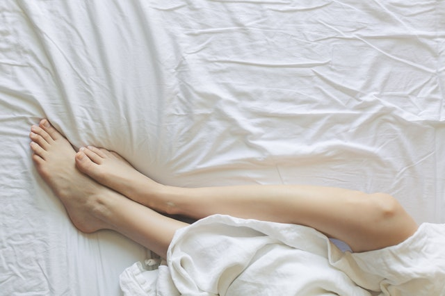 woman's feet in bed with white sheets and blankets