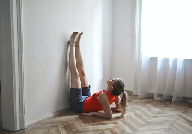 woman in work out clothes laying up on her elbows with her legs up against the wall
